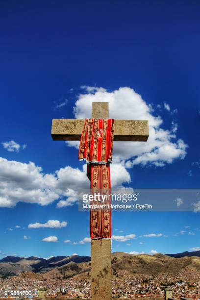 Low Angle View Of Cross On Landscape Against Blue Sky