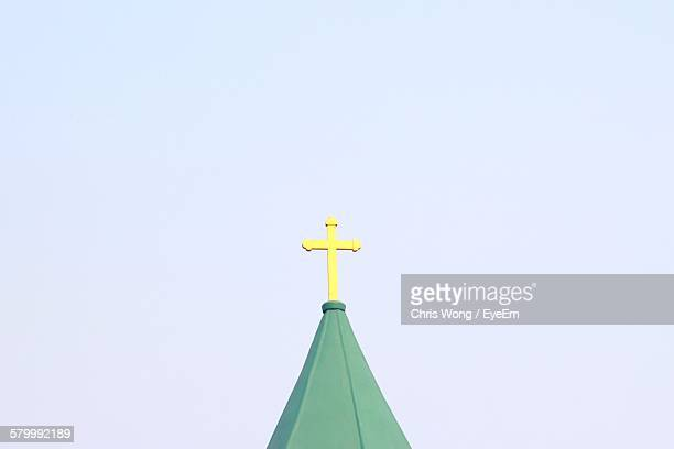 Low Angle View Of Cross On Spire Against Clear Sky