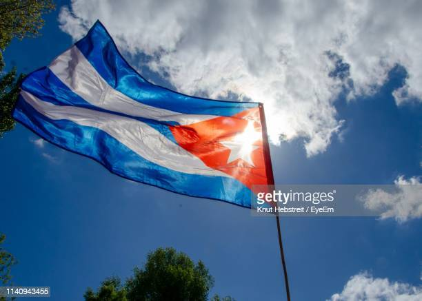 low angle view of cuban flag against blue sky - cuban flag stock pictures, royalty-free photos & images