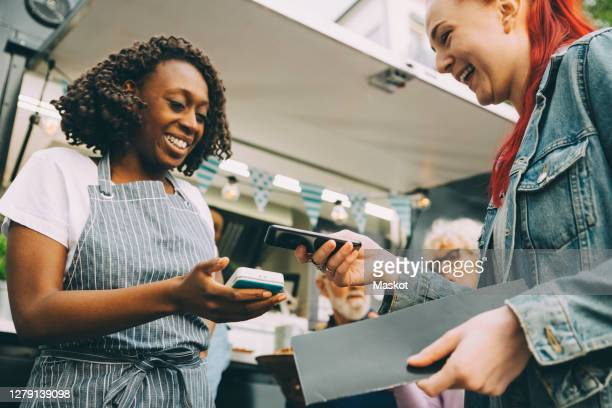 low angle view of customer paying through smart phone in city - small business stock pictures, royalty-free photos & images