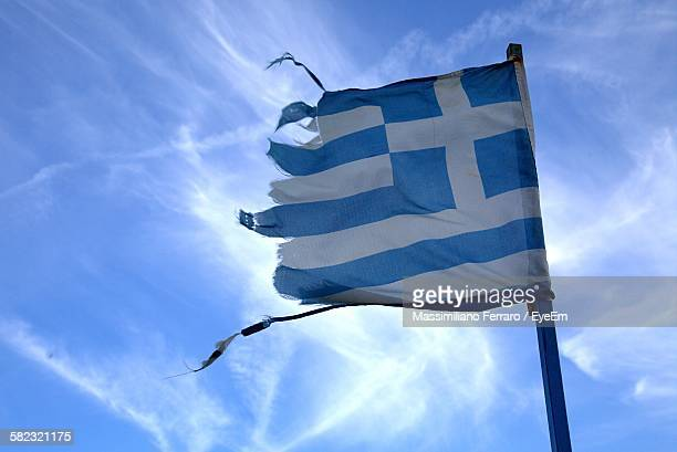 Low Angle View Of Damaged Greece Flag Against Sky