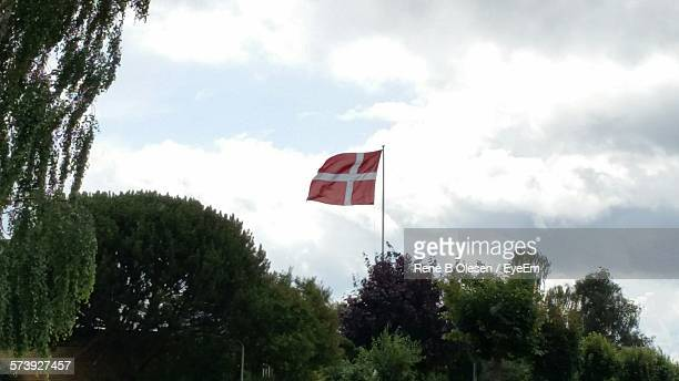 Low Angle View Of Danish Flag Amidst Trees Against Cloudy Sky