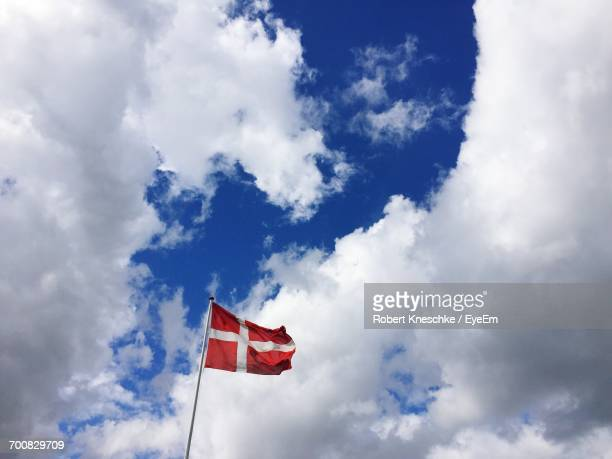 Low Angle View Of Danish Flag Waving Against Cloudy Sky