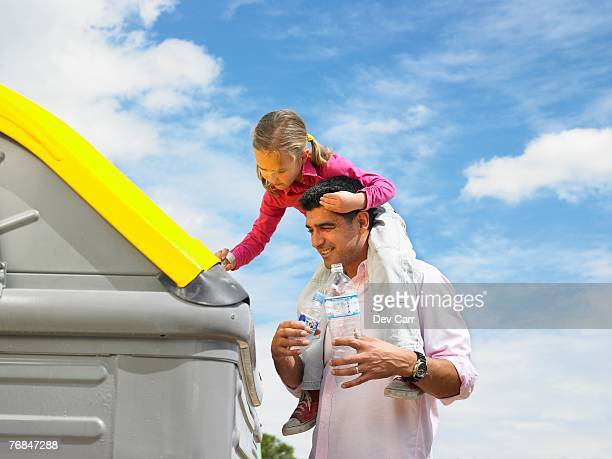 low angle view of daughter (5-7) on father's shoulders putting plastic bottle in recycling bin, alicante, spain, - reciclagem imagens e fotografias de stock