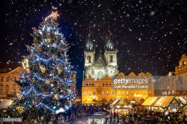 low angle view of decorated christmas tree and tyn church against sky during snowfall at night - notre dame de tyn photos et images de collection
