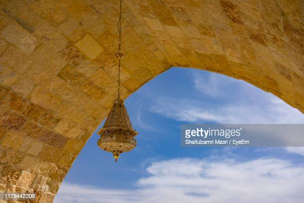 Low Angle View Of Decoration Hanging On Historic Arch Against Blue Sky
