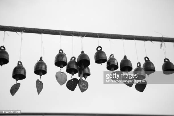low angle view of decorations hanging against clear sky - bell stock pictures, royalty-free photos & images