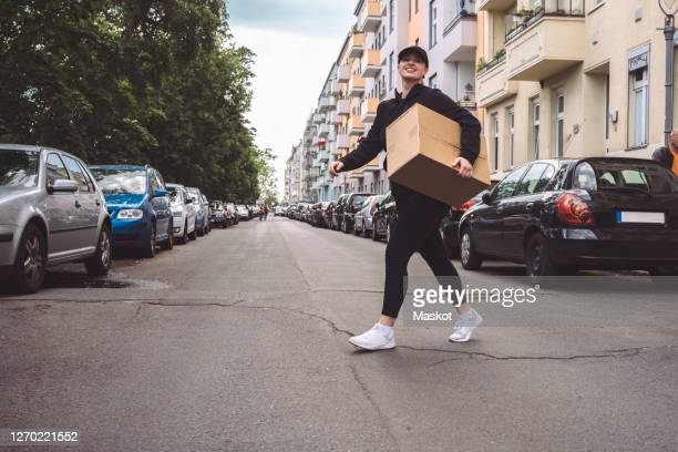 low angle view of delivery woman with cardboard box walking on street in city - junge frau allein stock-fotos und bilder
