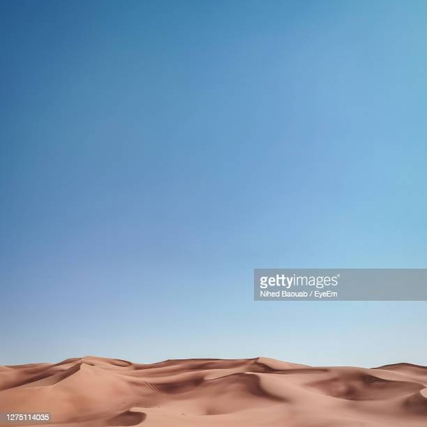low angle view of desert against clear blue sky - desert stock pictures, royalty-free photos & images