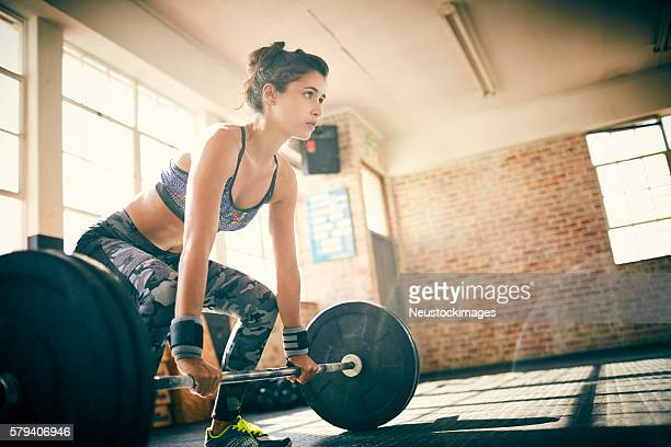 Low angle view of determined woman deadlifting with barbell