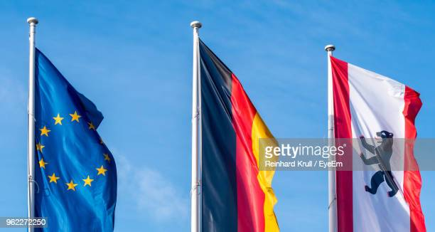 Low Angle View Of Different National Flags Against Blue Sky