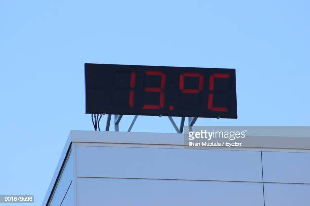 Low Angle View Of Digital Clock On Building Terrace Against Clear Sky