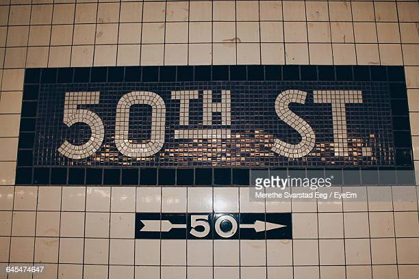 low angle view of directional sign on wall - number 50 stock photos and pictures