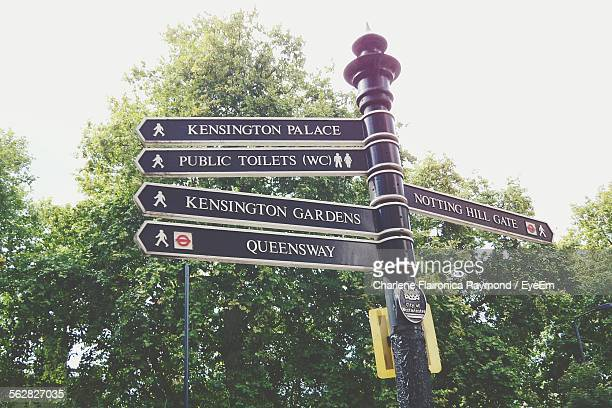 low angle view of directional signs against trees - bayswater stock pictures, royalty-free photos & images