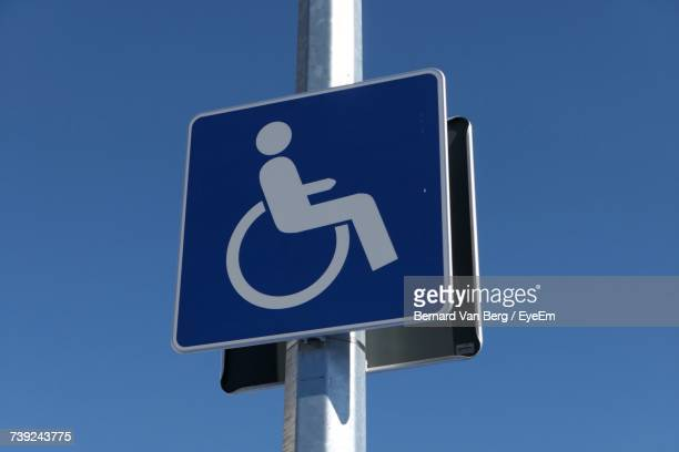 Low Angle View Of Disabled Sign On Pole Against Clear Sky