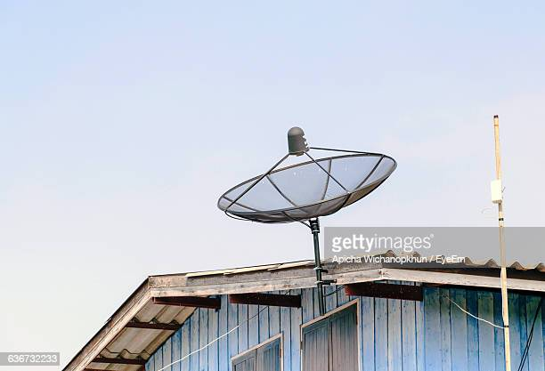 Low Angle View Of Dish Antenna Mounted On House Against Sky