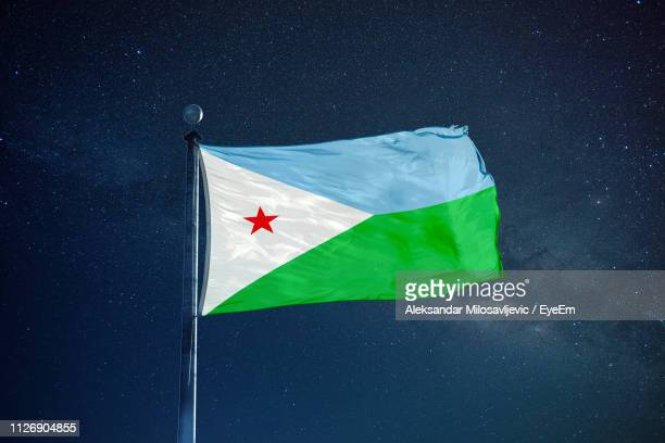 low angle view of djibouti flag against star field sky - djibouti stock pictures, royalty-free photos & images