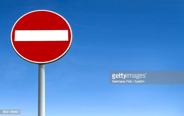 low angle view of do not enter sign against clear blue sky - verboten stock-fotos und bilder