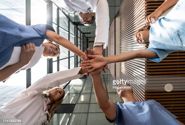 low angle view of doctor's and nurses all with hands in smiling at each other - civilian stock pictures, royalty-free photos & images