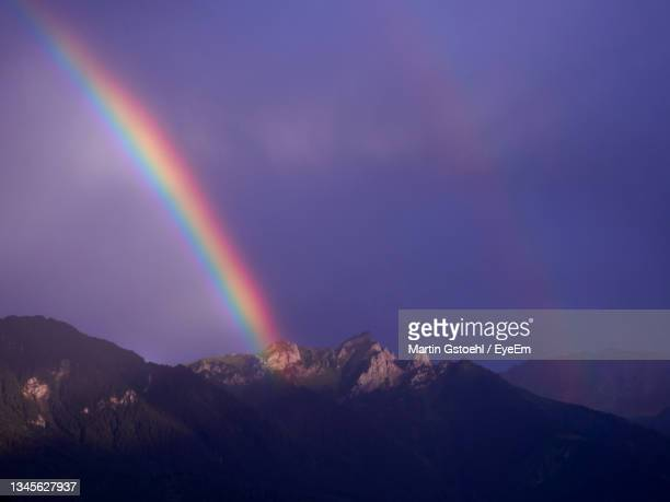 low angle view of double rainbow over mountains against sky - vaduz stock pictures, royalty-free photos & images