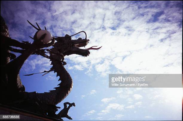 Low Angle View Of Dragon Statue Against Cloudy Sky