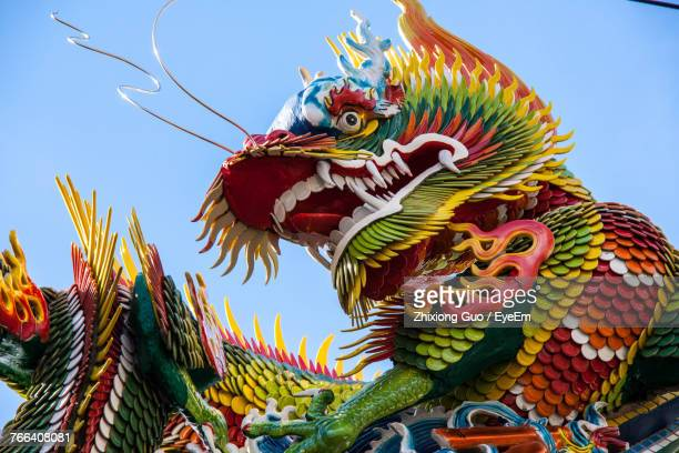 low angle view of dragon statue against sky - dragon stock photos and pictures