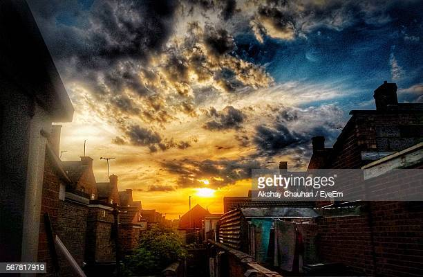 low angle view of dramatic sky over houses - leicester stock photos and pictures