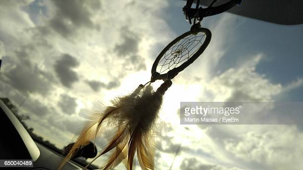 Low Angle View Of Dreamcatcher Hanging In Car Against Cloudy Sky