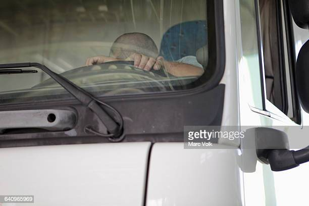Low angle view of driver sleeping in truck seen through windshield