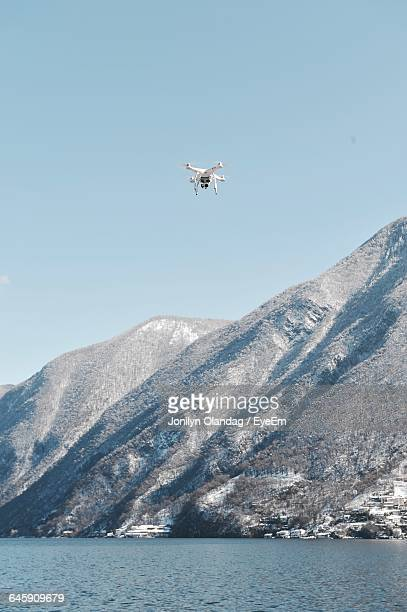 Low Angle View Of Drone Airplane Flying Over Lake By Mountains Against Sky