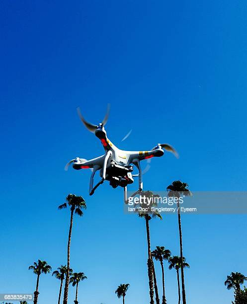 low angle view of drone and palm trees against clear blue sky - オクトコプター ストックフォトと画像