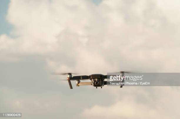 low angle view of drone flying against cloudy sky - drone foto e immagini stock