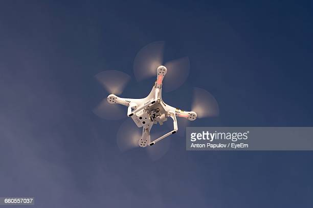 Low Angle View Of Drone Flying Against Sky On Sunny Day