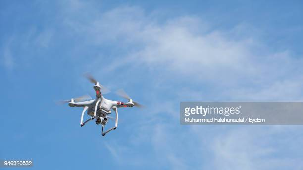 low angle view of drone flying against sky - drone photos et images de collection