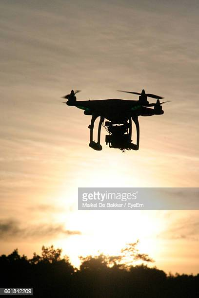 low angle view of drone flying in sky during sunset - オクトコプター ストックフォトと画像
