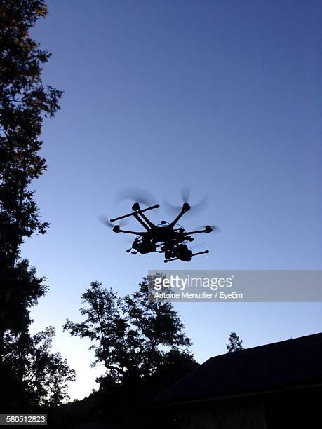 Low Angle View Of Drone With Camera Against Blue Sky