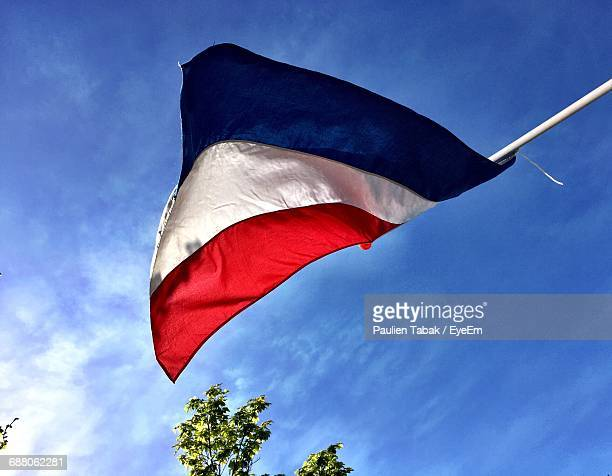 Low Angle View Of Dutch Flag Against Blue Sky