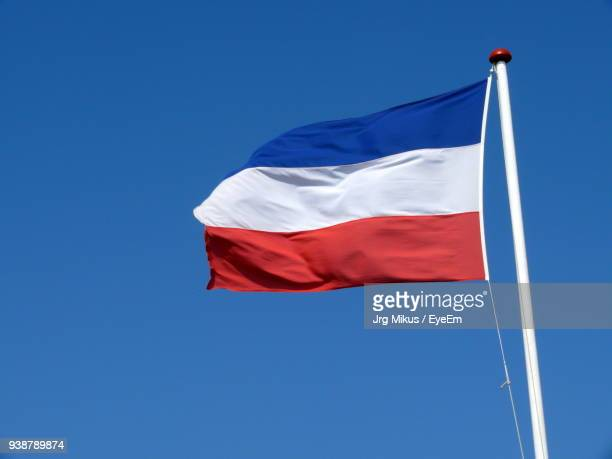 Low Angle View Of Dutch Flag Against Clear Blue Sky