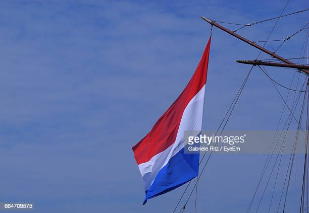 Low Angle View Of Dutch Flag On Mast Against Sky