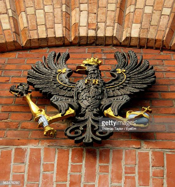 Low Angle View Of Eagle Sculpture On Brick Wall