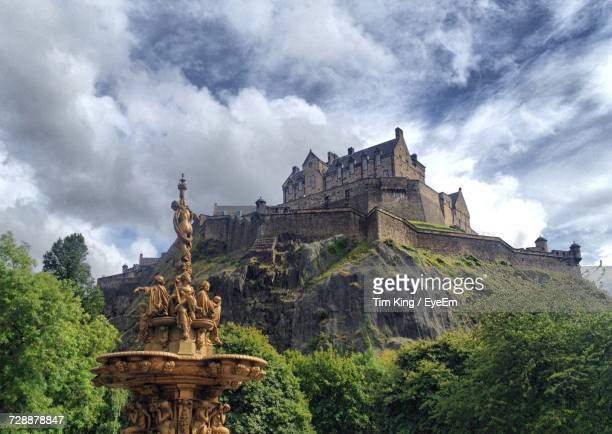 low angle view of edinburgh castle against cloudy sky - edinburgh scotland stock pictures, royalty-free photos & images