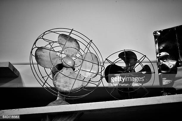 Low Angle View Of Electric Fans On Table Against Wall