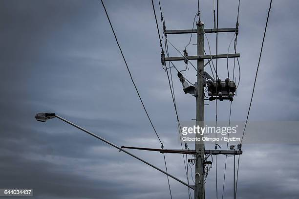 Low Angle View Of Electric Pole Against Cloudy Sky