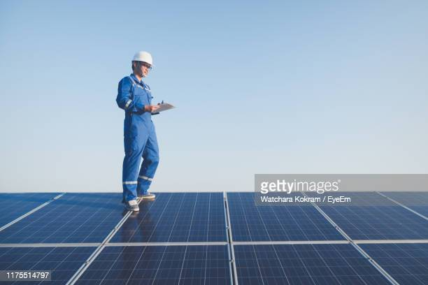 low angle view of electrician examining solar panels while standing against sky - power occupation stock pictures, royalty-free photos & images