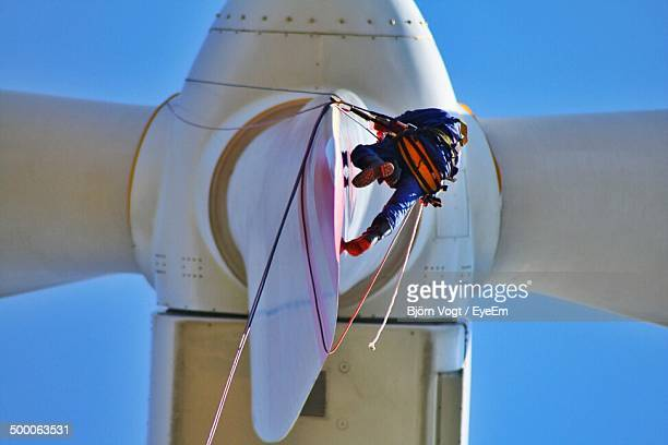 low angle view of electrician repairing windmill against clear blue sky - windmills stock photos and pictures