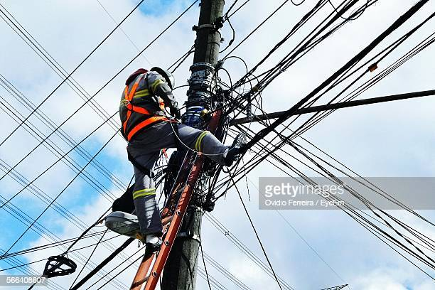 Low Angle View Of Electrician Working On Pole Against Cloudy Sky