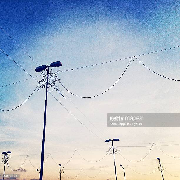 Low Angle View Of Electricity Poles Against The Sky