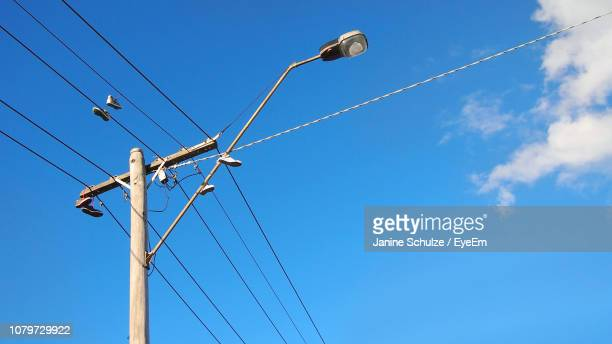 low angle view of electricity pylon against blue sky - power line stock pictures, royalty-free photos & images