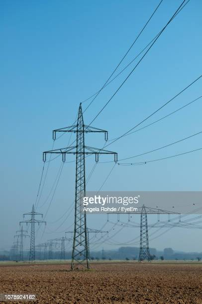 low angle view of electricity pylon against clear blue sky - angela rohde stock-fotos und bilder