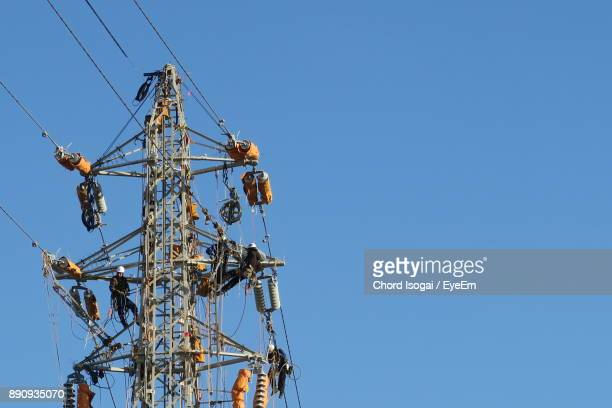 low angle view of electricity pylon against clear blue sky - isogai ストックフォトと画像
